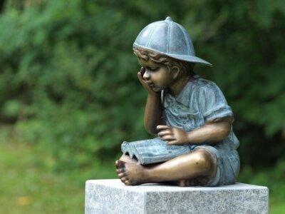 Bronzefigur Kind am lesen